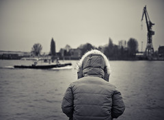 solitude in watching the boats passing by (pamela ross) Tags: blur men pen river person boat ship bokeh harbour crane hamburg olympus explore jacket 20mm elbe voigtlnder ep1 f095