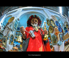 Water Vendor (iPh4n70M) Tags: africa red water rouge photography photo nikon eau photographer photographie traditional north agadir fisheye morocco photograph maroc tc souk vendor nikkor 16mm seller hdr photographe marchand tenue vendeur traditionnel souss 9xp d700 9rw tcphotography ph4n70m iph4n70m tcphotographie
