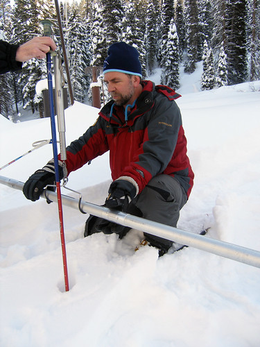 Abramovich balances the tube on the scale to get the weight of the tube and snow sample.
