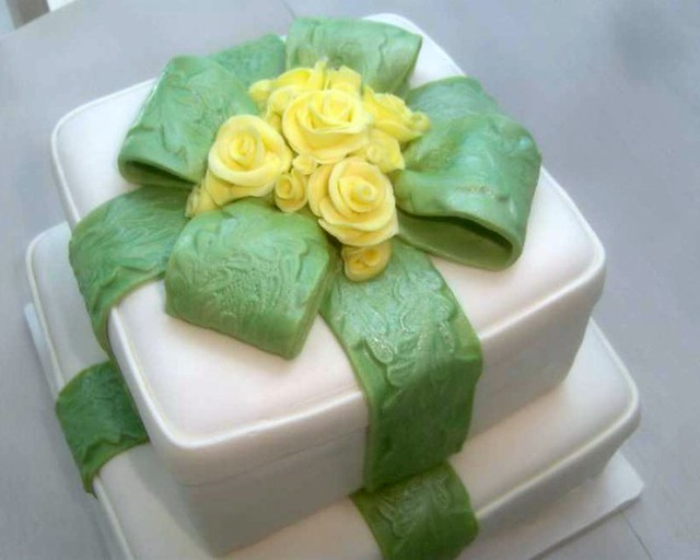 gift box cake with green embossed ribbon and yellow roses