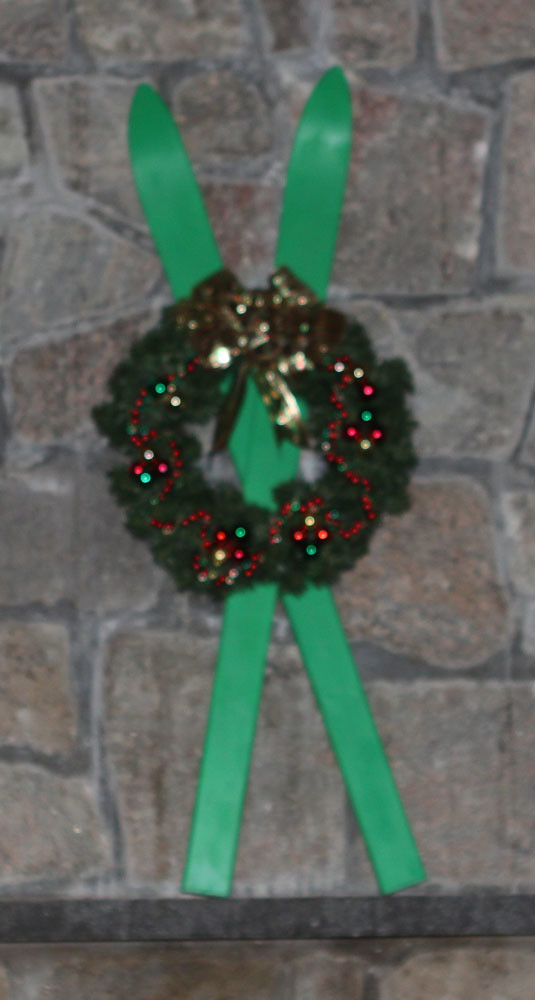 Christmas Evergreen wreath with red green and gold decorations set on upcycled green skis