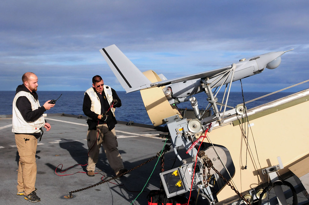 Men perform pre-flight checks on an unmanned aerial vehicle before launch.
