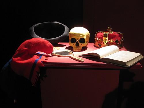 Photo aus dem Theatermuseum: Schädel, Krone, Spiegel, Buch auf einem Tisch