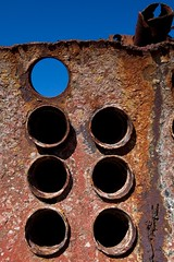 Rusty Art (ScottJphoto) Tags: blue sky art rust hole