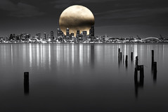 Supersized (Aaron Eakin) Tags: seattle city sea bw moon water skyline clouds buildings reflections washington skyscrapers fake super alki pugetsound pilings elliottbay obviously selectivecolor supersized shooped iwasmoreexcitedaboutthewriteupthanthephoto