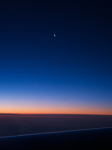 Sliver Waning crescent moon from my window seat on Virgin Atlantic this morning. The dot above the moon is either a blown pixel or the planet Venus.  (No, no, it