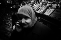 Woman at the Newsstand (Araakii) Tags: seattle street leica woman news abstract zeiss 35mm washington downtown phone veil market candid rangefinder east carl newsstand magazines pikeplace middle m9 firstpikenews biogon3528zm