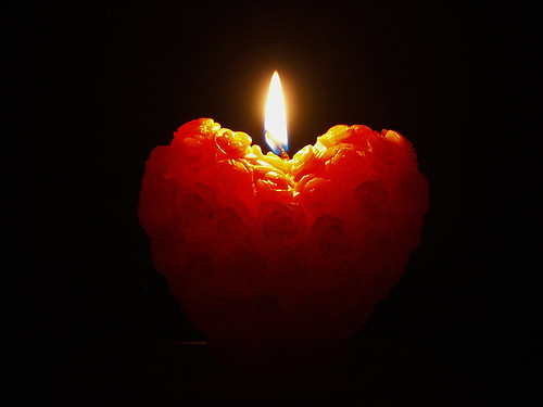 heart-shaped red candle burning