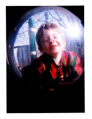 Lennon in Dimension 7 (Dead  Air) Tags: city trees boy sky sunlight distortion playground buildings portland holga surreal son bubble sciencefiction lennon iv psu todler fisheyelens d7 threeyearold piggynose coatofmanycolors dimension7 boyintheplasticbubble