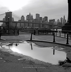 Evening. Brooklyn Bridge and Manhattan. (astikhin) Tags: road old city nyc newyorkcity bridge light shadow sky urban blackandwhite bw usa ny newyork black detail reflection building tree tower cars lamp car metal architecture brooklyn clouds america puddle us iron downtown outdoor streetlamp manhattan perspective landmark structure sidewalk transportation brooklynbridge manhattanbridge suspender suspensioncable wwwastikhincom