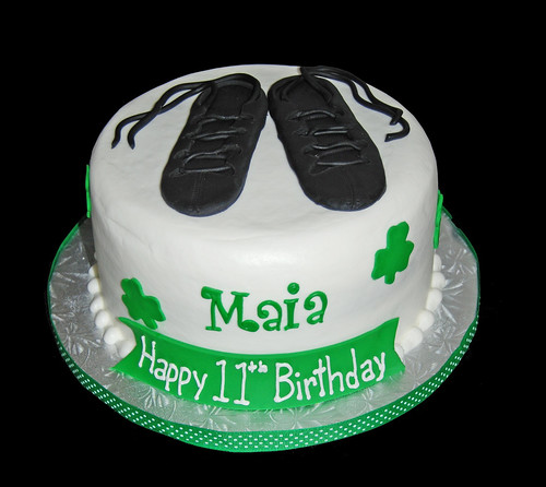 Green shamrock birthday cake topped with irish dancing shoes