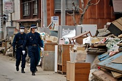 Police Walking the Streets Downtown Ishinomaki Miyagi Touhoku Japan Earthquake Tsunami Disaster 2011 (Carsten Knoche) Tags: people mountain water japan trash japanese sadness boat big crazy scary earthquake workers garbage downtown ship sad place mud destruction debris volunteers police wave tsunami tragedy iwate oil quake shake everything nothing volunteer turned tragic muck 90 miyagi destroyed tidal devastation toppled destruct destructed ishinomaki aweful devastated devastate dumbfounding