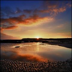 Sun setting over Pett Levels (adrians_art) Tags: sunset sea sky cloud beach water reflections coast sand horizon cliffs hills shore sunburst ripples eastsussex englishchannel winchelsea pettlevel cliffend