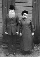 Mr and Mrs Lundström, Gävle, Gästrikland, Sweden (Swedish National Heritage Board) Tags: woman man standing beard outdoors couple hats husband older wife riksantikvarieämbetet theswedishnationalheritageboard