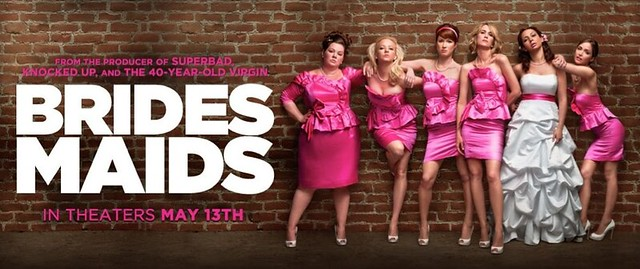 Bridesmaids poster: six women stand in front of a brick wall. Five of them are wearing pink bridesmaids dresses and the sixth is wearing a wedding dress. The title appears in bold white text.