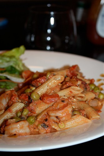 plate of ziti pasta covered in shrimp, peas, and red sauce with a side salad