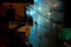 Foggy street at night (@n@nd@m) Tags: mist motion bike fog night buildings hotel town nikon neon running scooter vietnam wires shops nikkor sapa laocai d90