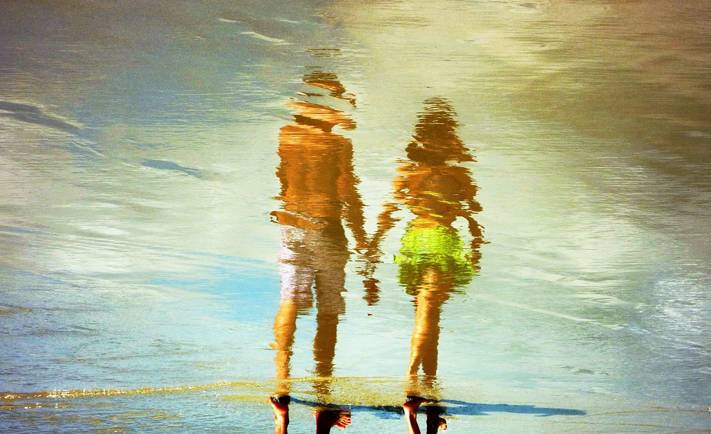 Water Art: A young couple walk hand in hand on a Brazilian beach