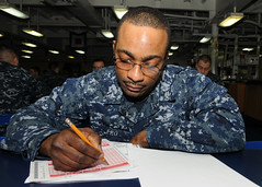 Sailor takes advancement exam aboard USS Peleliu.
