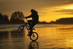 wheelie. (kvdl) Tags: sunset reflection beach bike silhouette march dof britishcolumbia springbreak tofino westcoast wheelie chestermanbeach kvdl canonef70200mmf28lisiiusm gettyimagescanada TGAM:photodesk=peakaction TGAM:photodesk=silhouette
