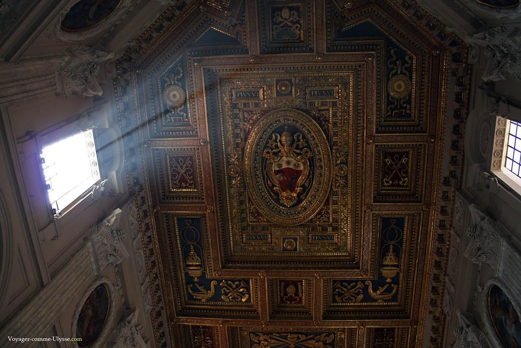 Au plafond, richement décoré de bois sculpté et doré, on reconnaît les armoiries papales