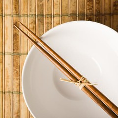 Chopsticks on an Empty Bowl (Passive Income Dream.com) Tags: wood stilllife food color horizontal closeup square asian dish empty pair lifestyle nobody bowl bamboo indoors placemat photograph simplicity chopsticks dining cropped inside tied utensil foodanddrink placesetting dinnerware traditionalculture tableware selectivefocus highangle tiedtogether