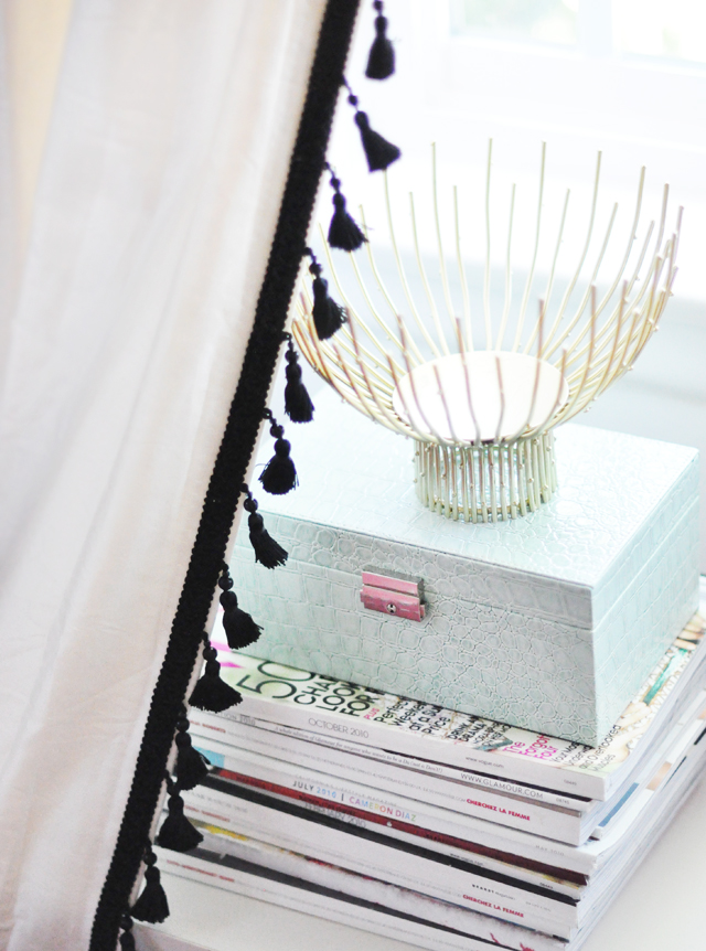 white curtains with black tassels + stack of magazines and jewelry box