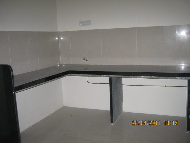 L Shaped Kitchen Platform with jet black granite top and piped gas connection in a flat at Sangria Towers at Megapolis Hinjewadi Phase 3, Pune