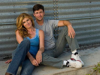 Tami and Eric Taylor seated on the ground in front of a wall