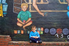 Regina Places her son next to his image in the mural 2