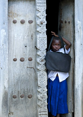 Kid going to school in Kilwa Kivinje village, Tanzania. (Eric Lafforgue) Tags: voyage africa door wood travel people house building vertical architecture tanzania outdoors photography wooden carved kid photographie child african entrance culture carve doorway porte maison enfant oldbuilding bois swahili afrique eastafrica entree pleinair tanzanian tansania buildingentrance tanzanya tanzanie exterieur lookingatcamera colorpicture photocouleur 0261 decrepi tansaania tanzanija afriquedelest  enhauteur  colourpicture   kilwakivinje  regardcamera sculptee  tanznija  tanzniy tananja