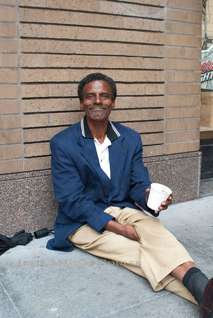 A homeless man in San Francisco smiles big for the camera as he sits on the sidewalk begging.