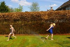 (Lottie45) Tags: girls summer brown sun green grass hat garden fun women shadows dress running sprinkler hedge females