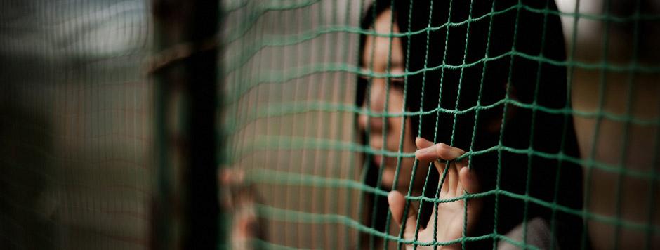Fotografía de una chica japonesa pegada a una valla con sus manos entre la alambrada