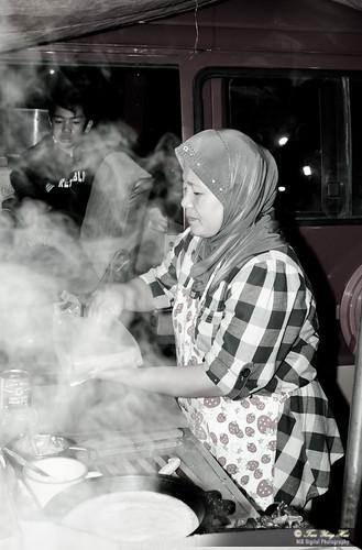 Makcik working hard behind the steam