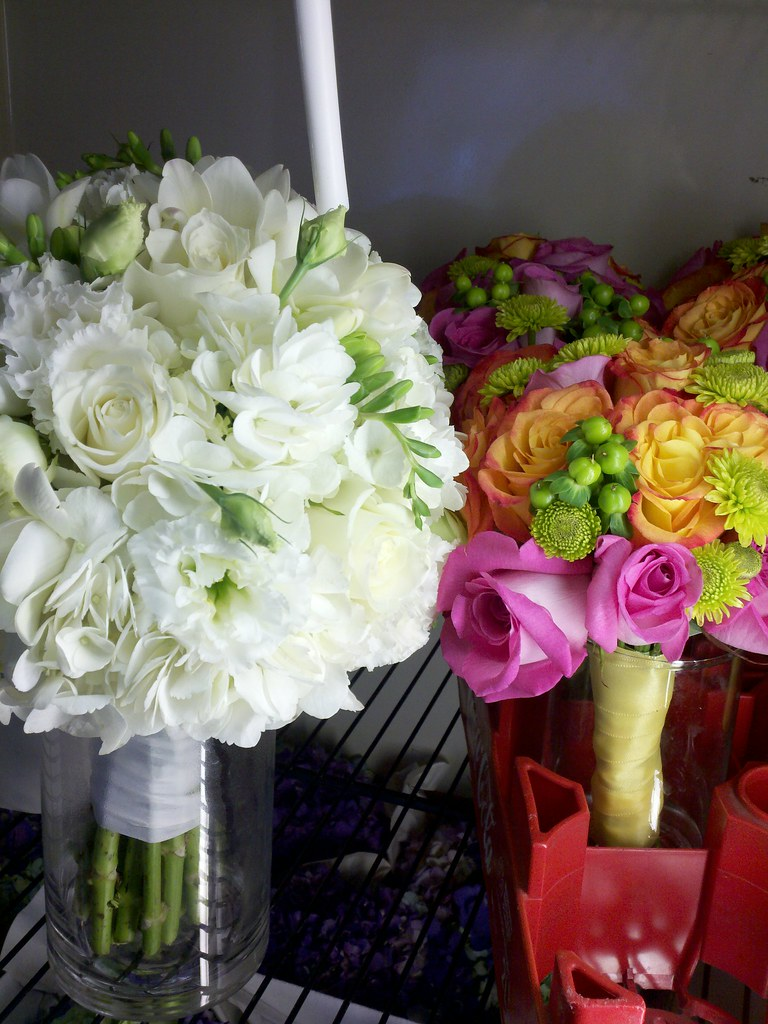 White bridal bouquet with bright colored bridesmaid bouquets