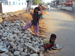 Children carry rocks for road construction