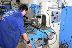 Un alumno del PCPI realizando prácticas del módulo de mecánica industrial con una máquina en el taller.