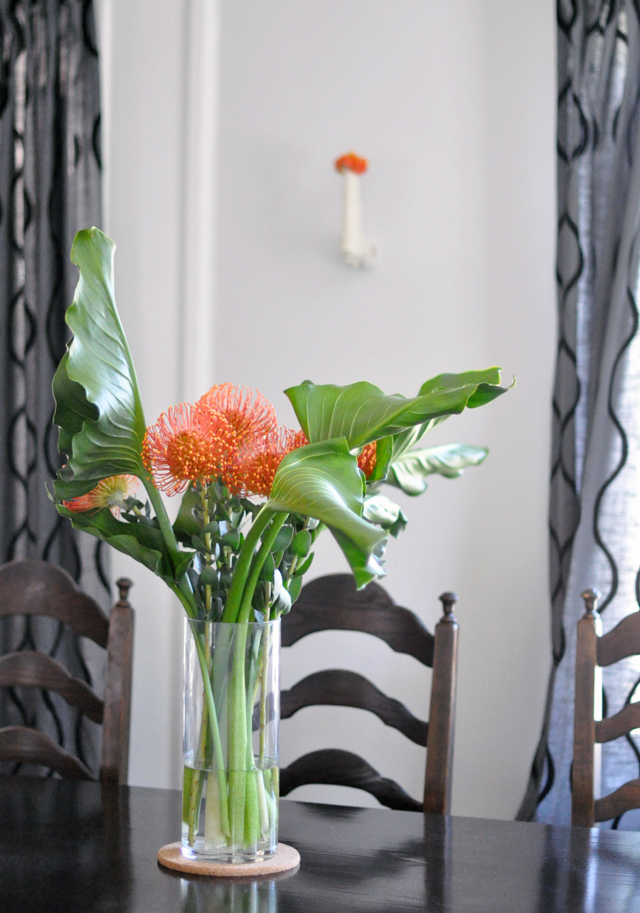 dining room table + orange flowers + gun vase