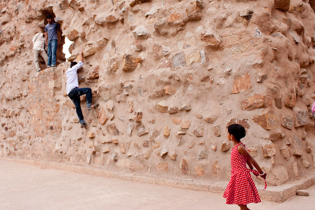 Girl watching boys climb at the Qutb Complex
