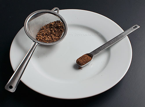 Roasted Sichuan Peppercorns, Ground Powder in measuring spoon, husks in a strainer
