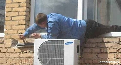 Man leaning out of window fitting aircon