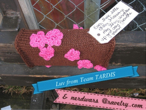 Hello Sweetie!  Yarnbombing by team TARDIS - brown background with pink crocheted cherry blossoms wrapped around a horizontal wood piece on a bench