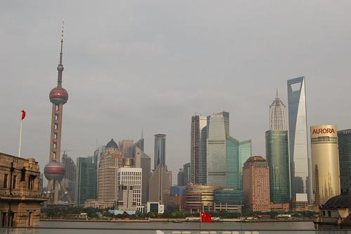 Oriental Pearl Tower, Shanghai World Financial Center und Jin Mao Tower mit roter Fahne im Vordergrund unter einem eher diesigen Himmel