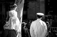 A young girl in white dress admiring a man in white uniform. (sinisa ostojic) Tags: street leica light bw man film girl analog blackwhite marine uniform kodak availablelight ambientlight young streetphotography brisbane parade sailor moment lookingdown tmax400 m6 anzac blanconegro anzacday leicam6 admiration xtol whitedress whiteuniform sinisaostojic