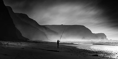 the one at the beach... (ibo.h) Tags: beach fisherman dark sunset clouds wind portugal algarve costavincentina