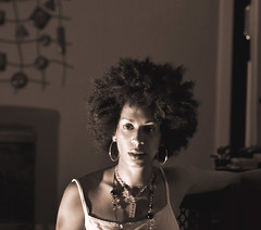 Retro Afro (CheekyAngels (catching up )) Tags: light shadow portrait woman selfportrait black girl face earings rock metal sepia female beads nikon focus dof bokeh afro flash gothic perspective retro jewellery stare caribbean freckles lipstick jamaican tamron 90mm lipgloss curlyhair strobe mixedrace ringlets ingot d5000 texturedhair retroafro