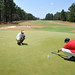 Alumnus Chris Hartwiger (right) checks putting green speed on the 2nd hole of Pinehurst No. 2 during a break in US Women's Open action.