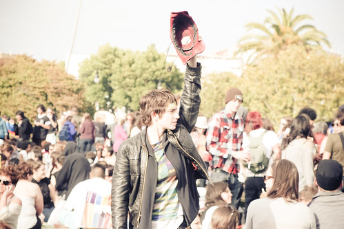 Androgynous pale person wearing a leather jacket and a t-shirt, standing in a crowd and holding up a hand with a baseball glove on it.