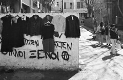 (ssj_george) Tags: road street camera old city ladies people film me shop wall analog writing 35mm walking lens outside greek 50mm graffiti town clothing women focus grafitti symbol asahi pentax grafiti scanner cyprus super iso clothes shirts xp2 400 graffitti scanned hanging anarchy epson analogue manual asa language foreigners tops ilford perfection skirts hangers walled asa400 nicosia f17 v330  georgestavrinos ssjgeorge  giorgosstavrinos